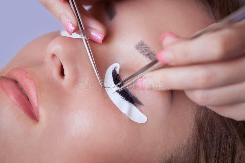 El amo del maquillaje corrige, y consolida los haces de las pestañas, sosteniendo hacia fuera un par de pinzas foto de archivo
