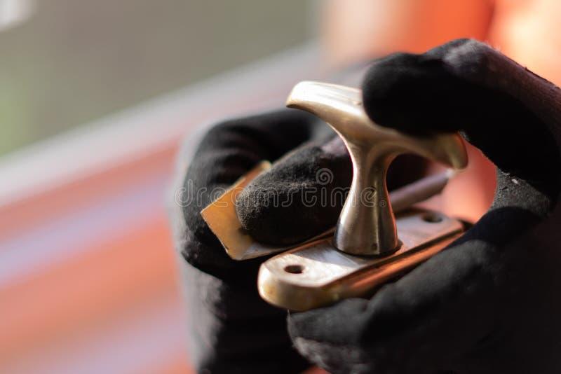 El amo en guantes negros recupera, pule la manija de ventana de cobre de cobre amarillo fotografía de archivo libre de regalías