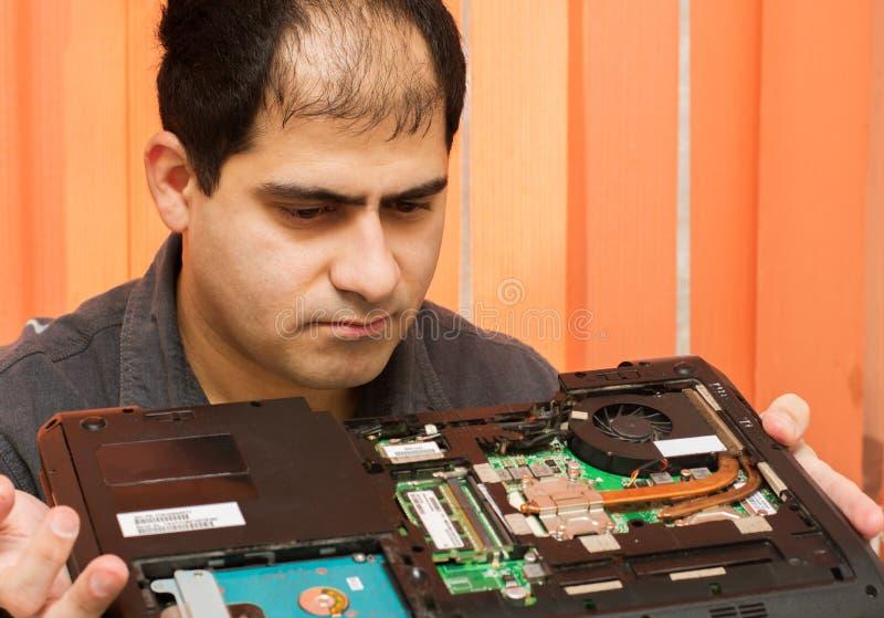 El amo examina el ordenador portátil imagen de archivo