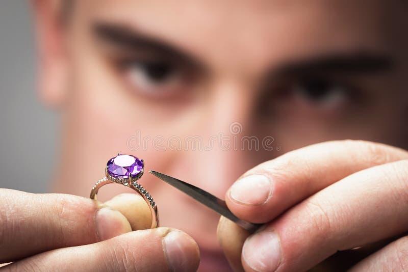 El amo examinará la joyería para los defectos fotos de archivo