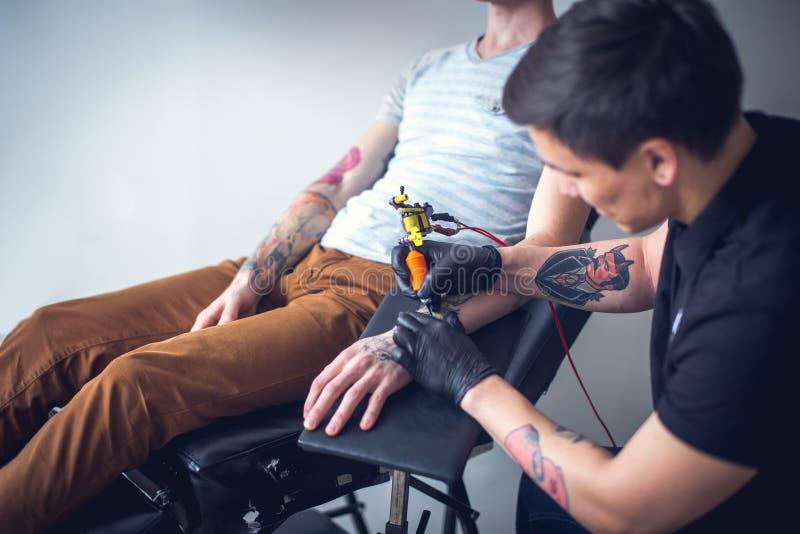 El amo hace el tatuaje en estudio del tatuaje fotos de archivo