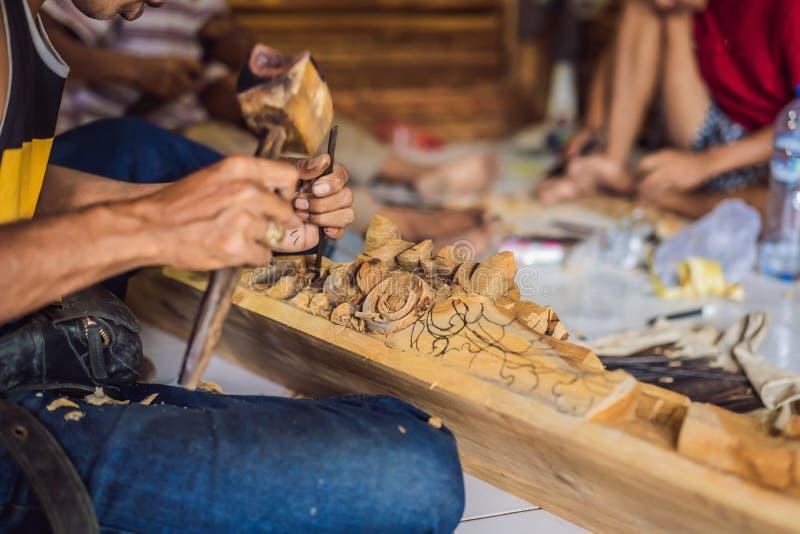 El amo madera-Carver hizo usando un plato nacional de madera del cuchillo especial - una cucharón con una manija modelada Un frag fotos de archivo