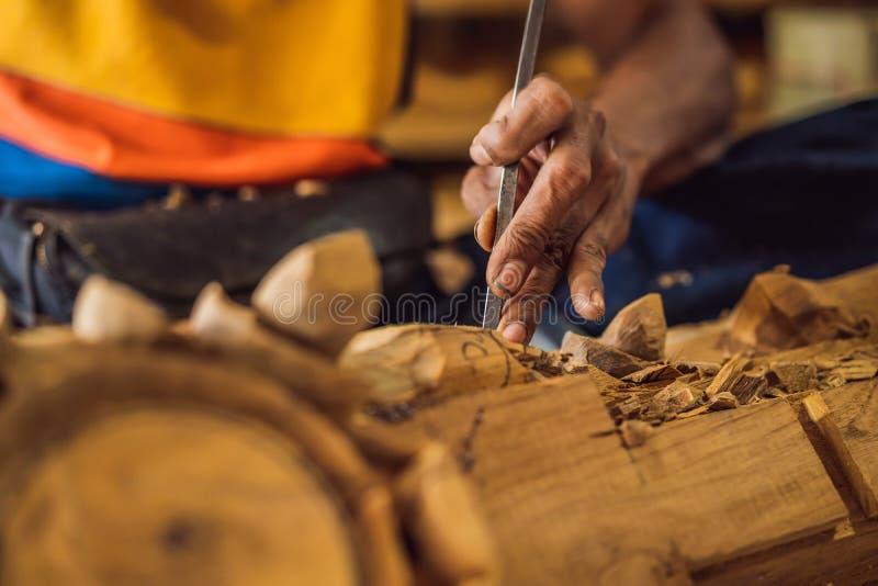 El amo madera-Carver hizo usando un plato nacional de madera del cuchillo especial - una cucharón con una manija modelada Un frag imágenes de archivo libres de regalías