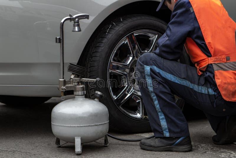 El amo masculino cambia la rueda y bombea los neumáticos usando un compresor foto de archivo