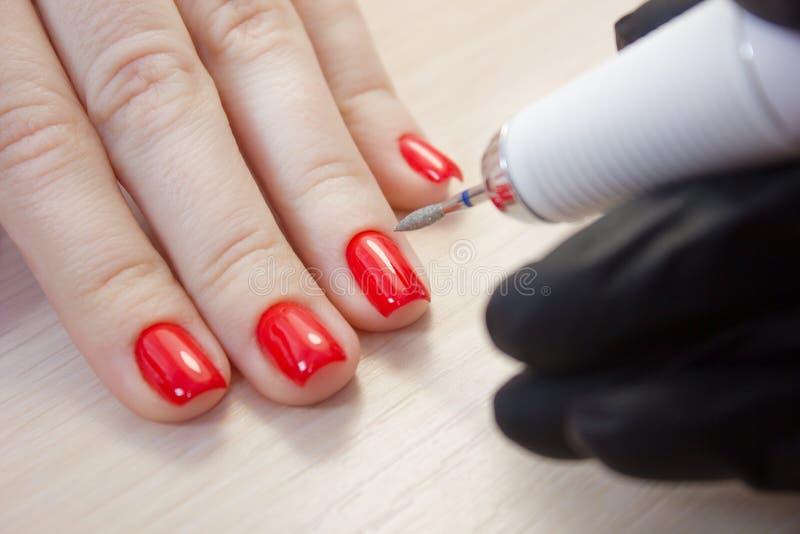 El amo utiliza una máquina eléctrica para quitar al esmalte de uñas en las manos del cliente durante manicura del hardware en el  foto de archivo libre de regalías