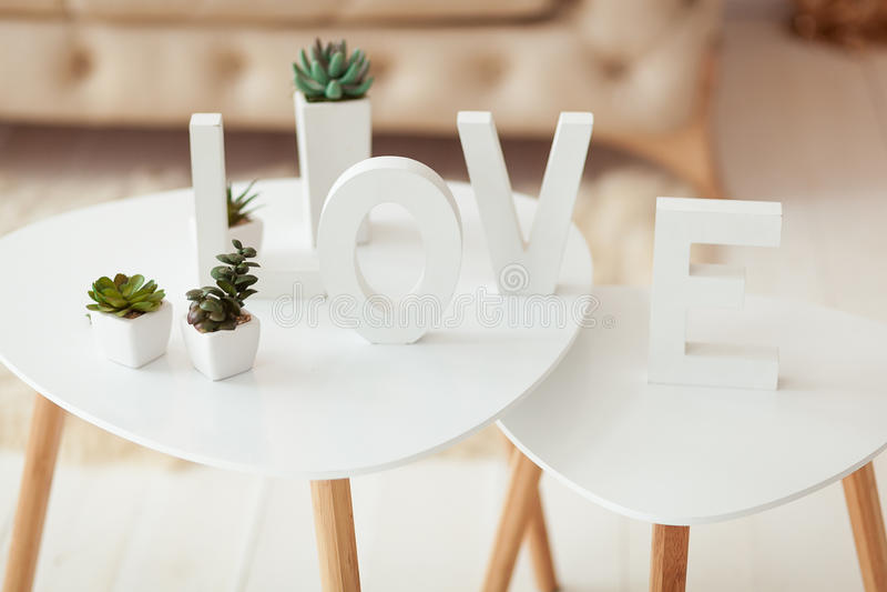 El amor de la palabra en las letras blancas en el fondo interior del volumen Sofá y mesa de centro blancos beige en el cuarto fotografía de archivo libre de regalías