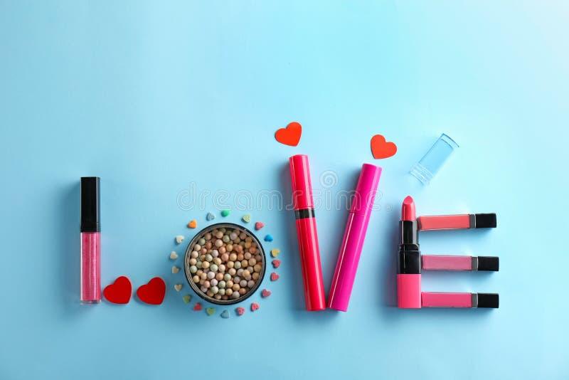 El AMOR de la palabra hizo de cosméticos decorativos en fondo del color imagen de archivo libre de regalías