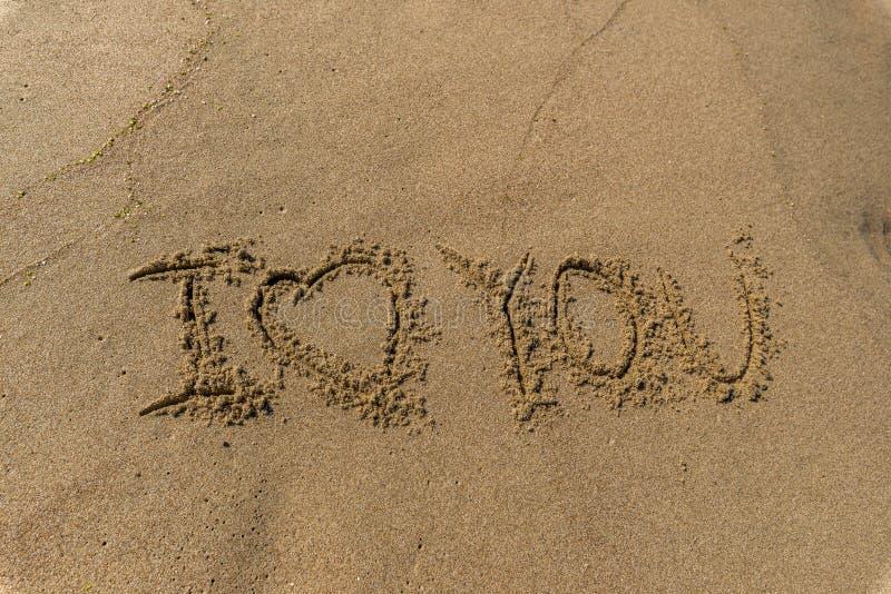 El amor de la palabra usted escrito en la arena en una playa foto de archivo libre de regalías