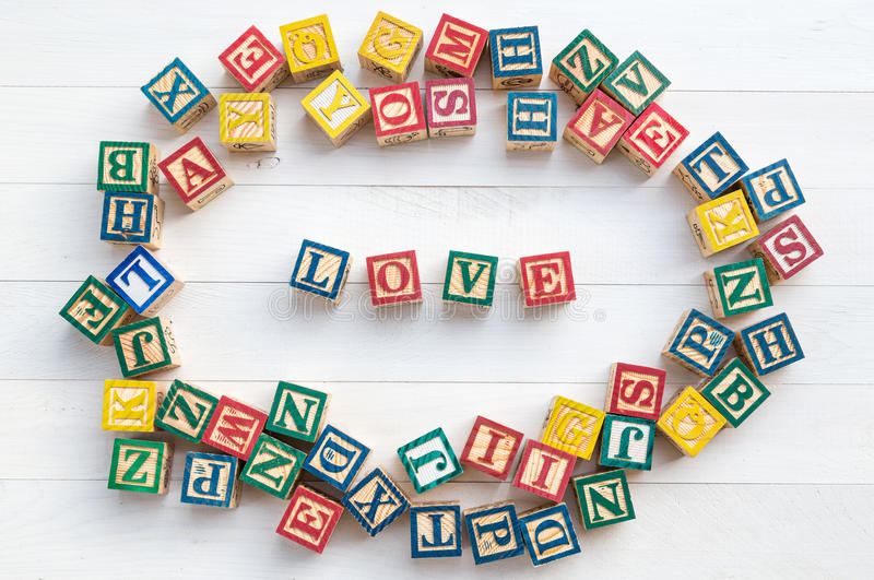 El AMOR escribe en bloque de madera del alfabeto en el fondo de madera blanco imagen de archivo libre de regalías