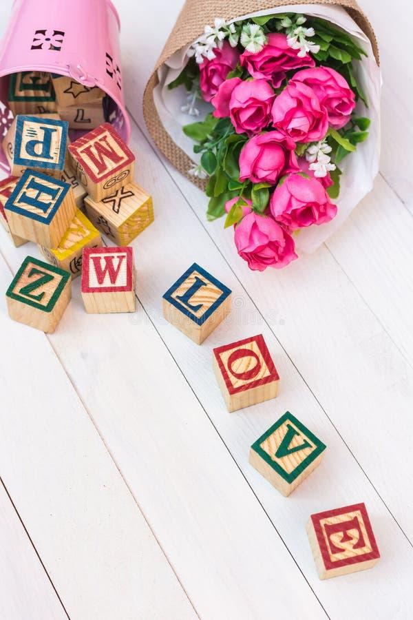 El AMOR escribe en bloque de madera del alfabeto en el fondo de madera blanco foto de archivo libre de regalías