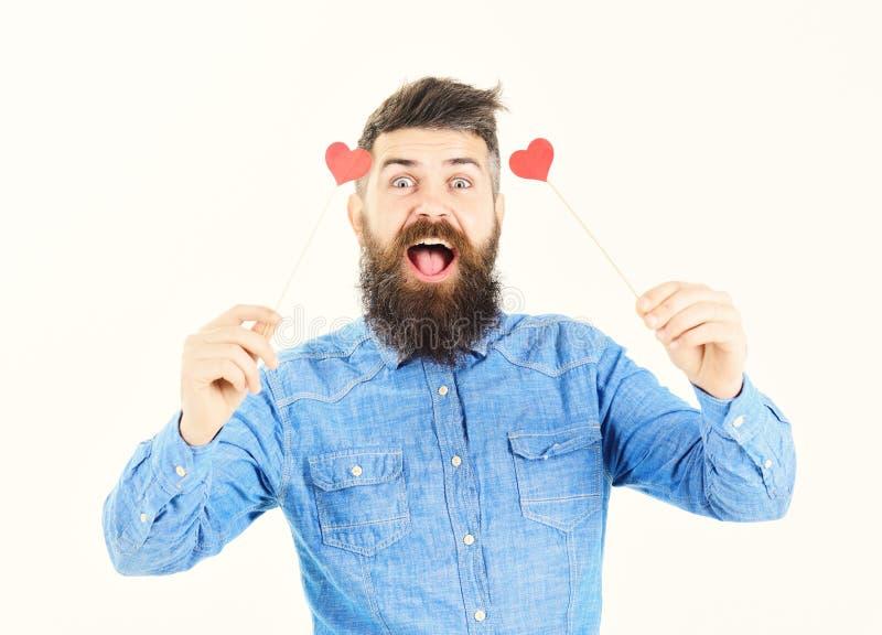 El amor está en el aire Hombre hermoso que sostiene la tarjeta en forma de corazón de la tarjeta del día de San Valentín con sonr fotos de archivo