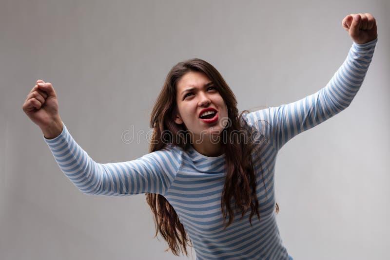 El animar exultante victorioso de la mujer joven fotos de archivo