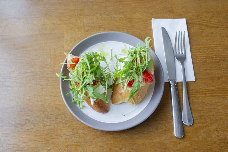 El antipasto italiano curruscante hecho en casa fresco llamó Bruschetta remató con el tomate, el ajo y la albahaca imagen de archivo