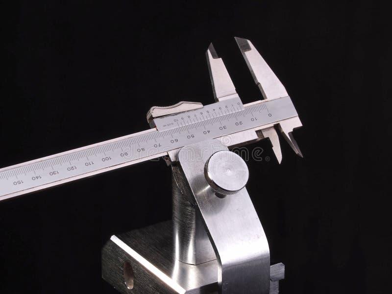 El aparato de medición métrico del calibrador a vernier en un cromo plateó el tenedor foto de archivo