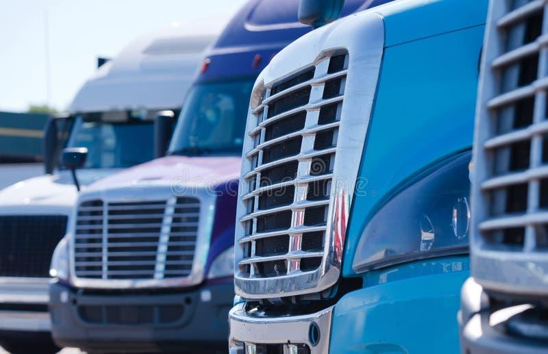 El aparejo grande semi acarrea parrillas de los tractores en fila en la parada de camiones imagenes de archivo