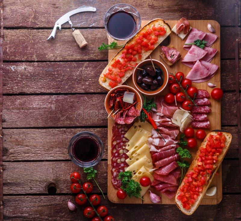 El aperitivo de la carne y del queso fijó para el vino rojo en fondo rústico, flatlay, copia el espacio fotografía de archivo libre de regalías