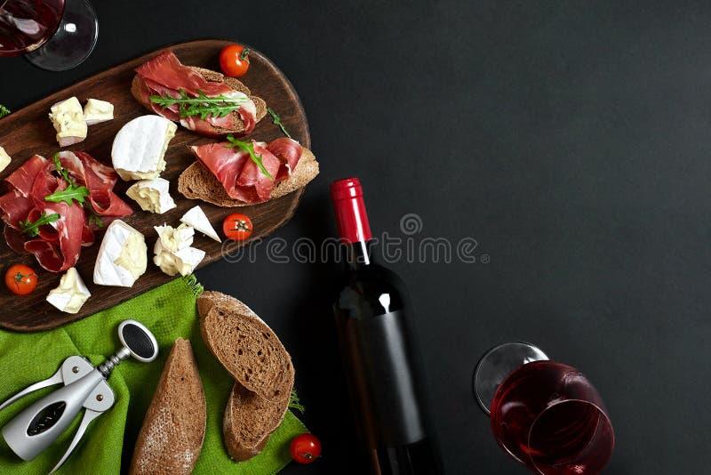 El aperitivo delicioso a wine - jamón, queso, rebanadas del baguette, tomates, sirvió en un tablero de madera, y el vidrio con el fotografía de archivo