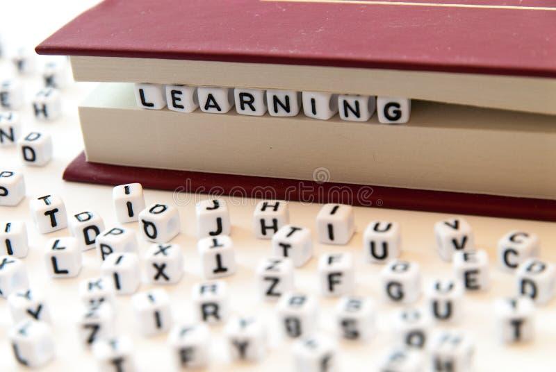 El aprendizaje de la palabra escrito con las letras entre un libro pagina el fondo blanco con las letras separadas alrededor de c fotografía de archivo libre de regalías