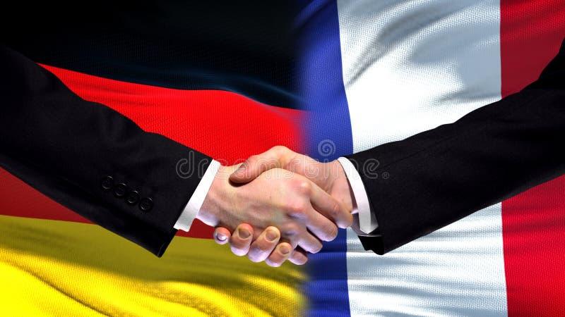 El apretón de manos de Alemania y de Francia, las relaciones internacionales de la amistad señala el fondo por medio de una bande fotos de archivo