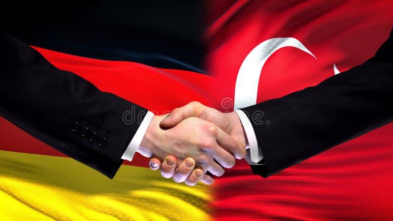 El apretón de manos de Alemania y de Turquía, las relaciones internacionales de la amistad señala el fondo por medio de una bande imagenes de archivo