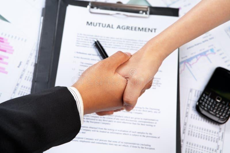 El apretón de manos btween a la empresaria sobre el acuerdo imagen de archivo libre de regalías