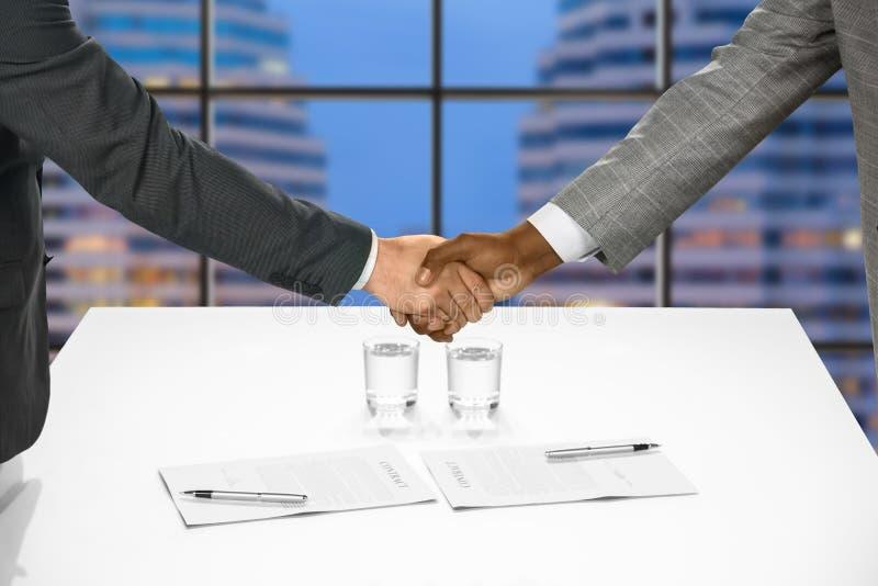 El apretón de manos de los hombres de negocios después de firmar los papeles foto de archivo