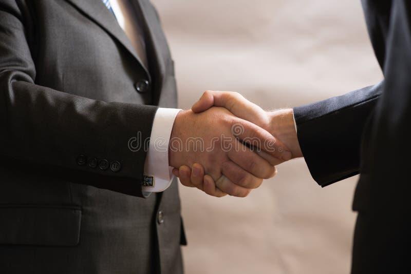 El apretón de manos del negocio de dos hombres de negocios en trajes, negocia y hace un trato imágenes de archivo libres de regalías