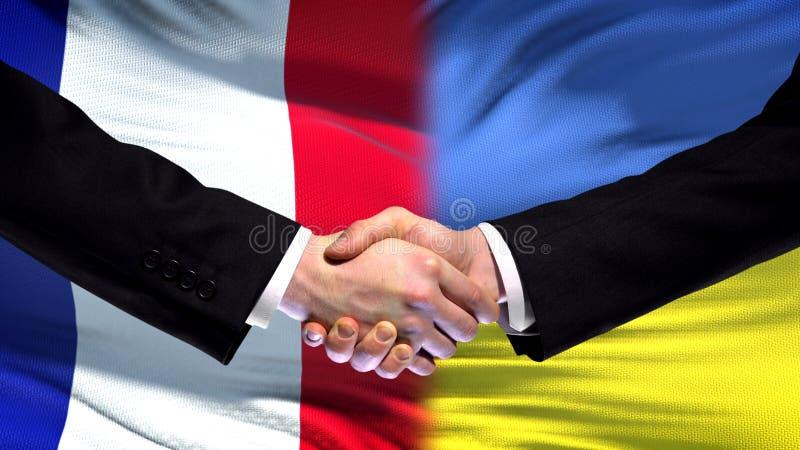 El apretón de manos de Francia y de Ucrania, las relaciones internacionales de la amistad señala el fondo por medio de una bander foto de archivo