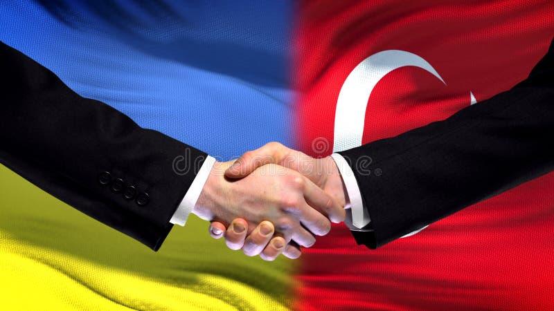 El apretón de manos de Ucrania y de Turquía, las relaciones internacionales de la amistad señala el fondo por medio de una bander fotos de archivo