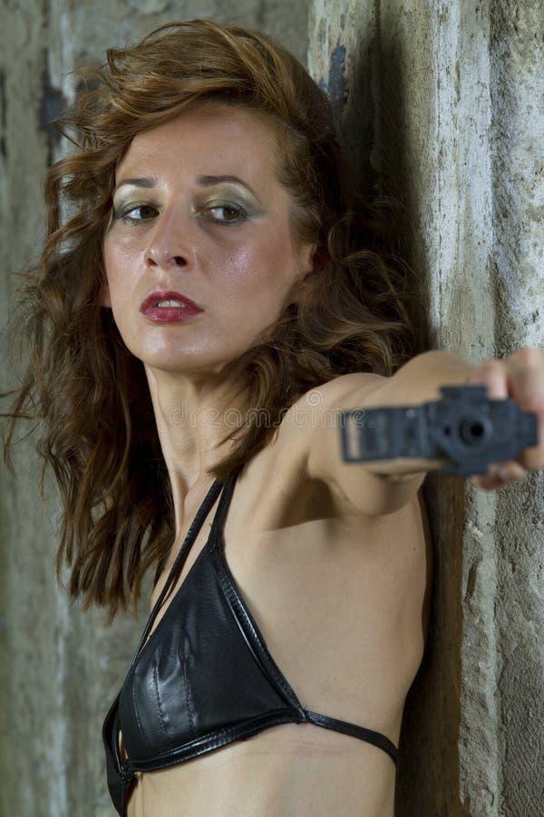 El apuntar atractivo de la mujer del arma imagen de archivo libre de regalías