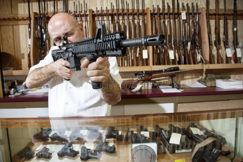 El apuntar mercantil maduro con el rifle en tienda de armas imágenes de archivo libres de regalías