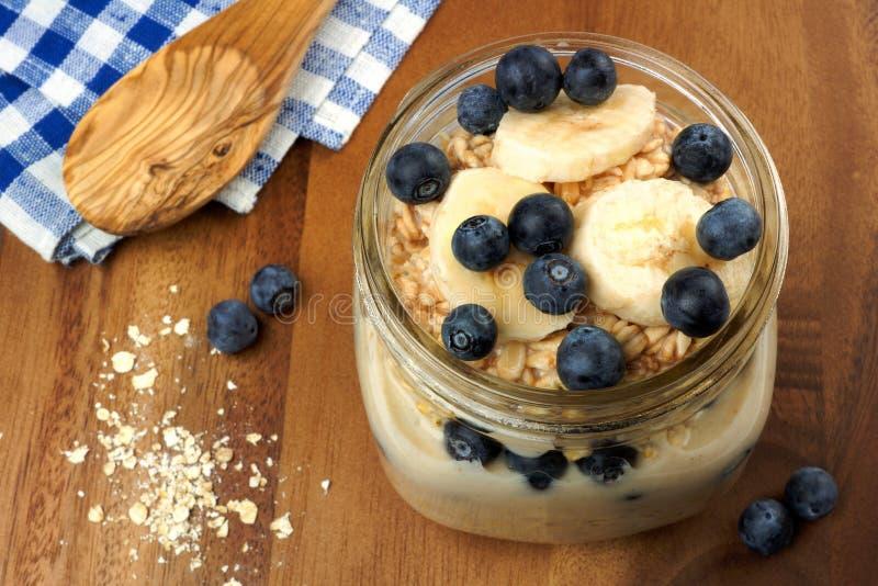 El arándano y el plátano desayunan harina de avena de noche en tarro de albañil foto de archivo libre de regalías