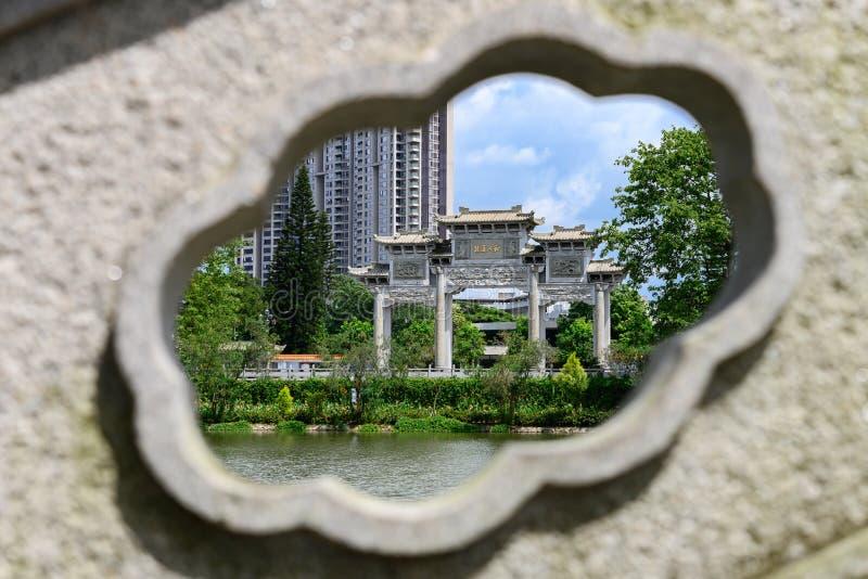 El arco chino tradicional enmarcado por la piedra que talla la traducción de los caracteres chinos es armonioso imagenes de archivo