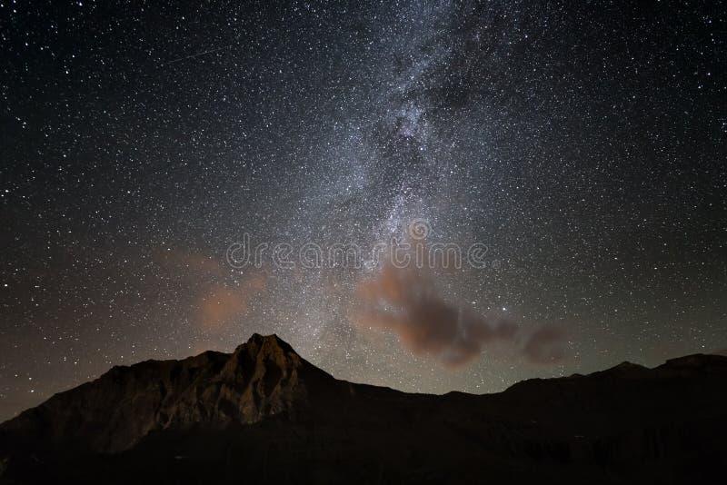 El arco colorido de la vía láctea que brilla intensamente y el cielo estrellado del alto para arriba en las montañas fotografía de archivo
