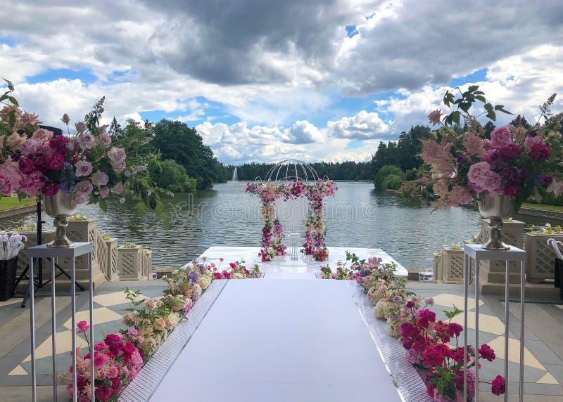 El arco de la boda adornó las flores al aire libre Disposici?n de la boda Ceremonia de boda en la playa en el parque Luz natural  imagenes de archivo