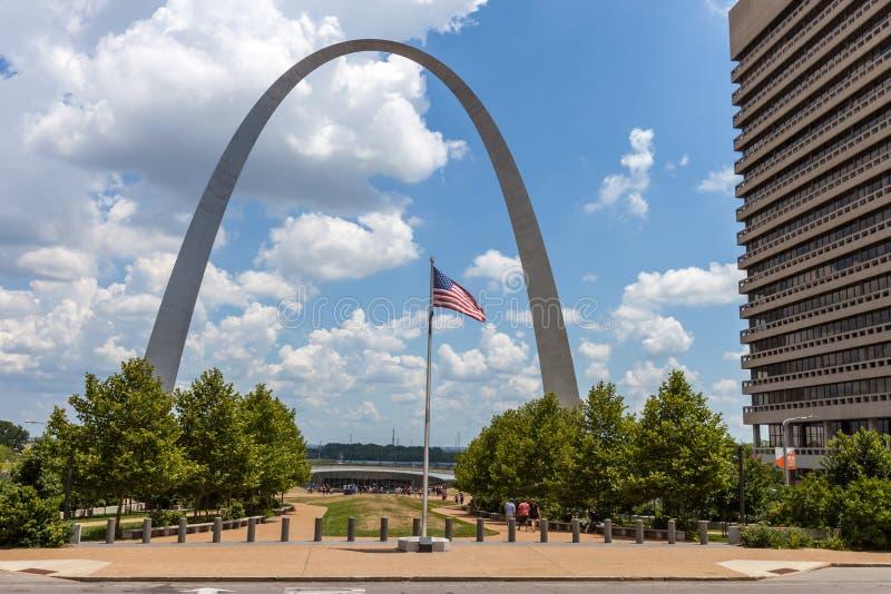 El arco de la entrada en St. Louis, Missouri con la bandera americana i foto de archivo
