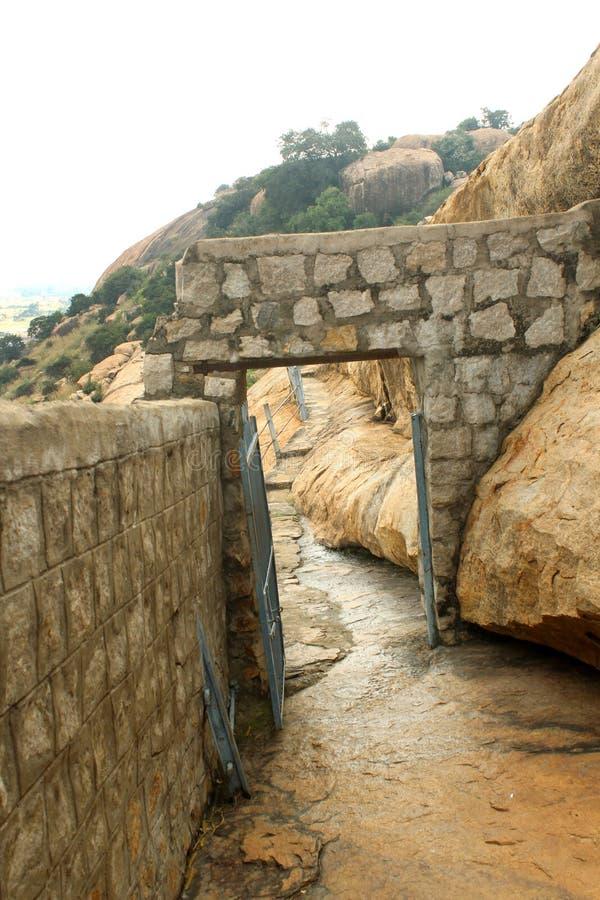 El arco de piedra de la manera a las camas de piedra jain en el complejo sittanavasal del templo de la cueva fotografía de archivo libre de regalías