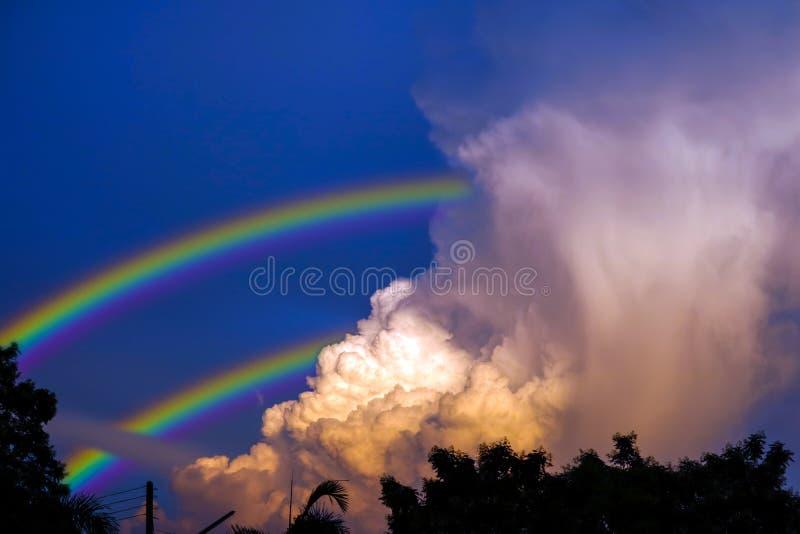 el arco iris aparece en cielo después de la lluvia y de la parte posterior en la nube de la puesta del sol fotos de archivo