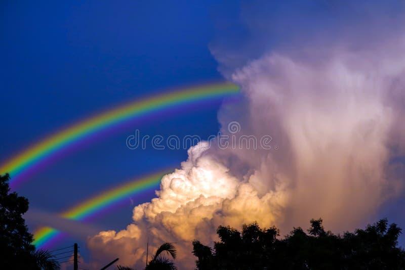 el arco iris aparece en el cielo después de la lluvia y de la parte posterior en la nube de la puesta del sol imagenes de archivo