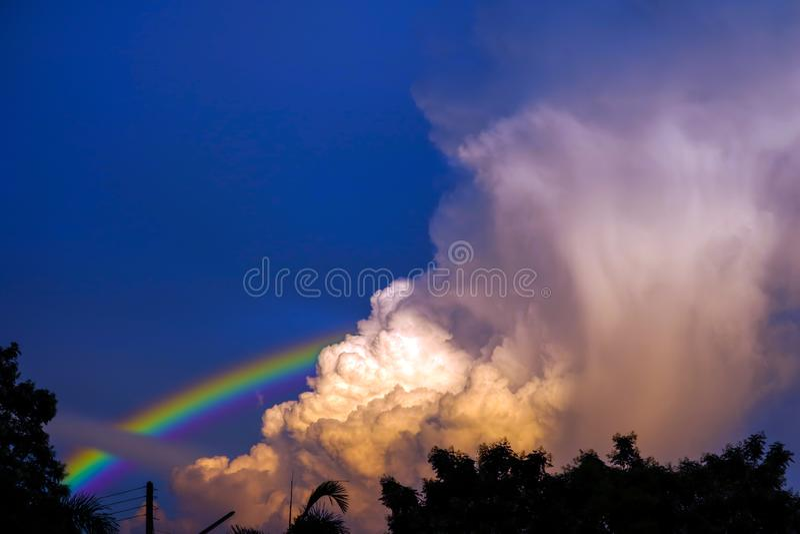 el arco iris aparece en el cielo despu?s de la lluvia y de la parte posterior en la nube de la puesta del sol fotos de archivo libres de regalías