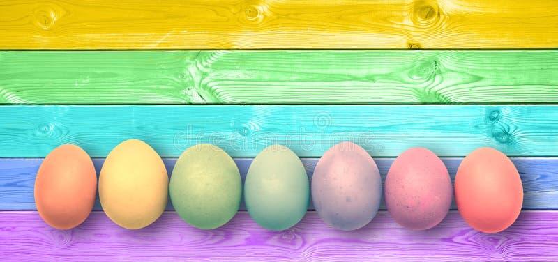 El arco iris colorido en colores pastel pintó los huevos, tablones de madera panorámicos, fondo de pascua foto de archivo