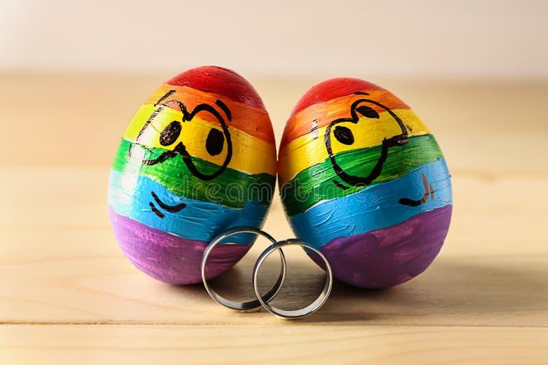 El arco iris pintó los huevos con los anillos de compromiso en la tabla de madera Concepto de LGBT imagenes de archivo