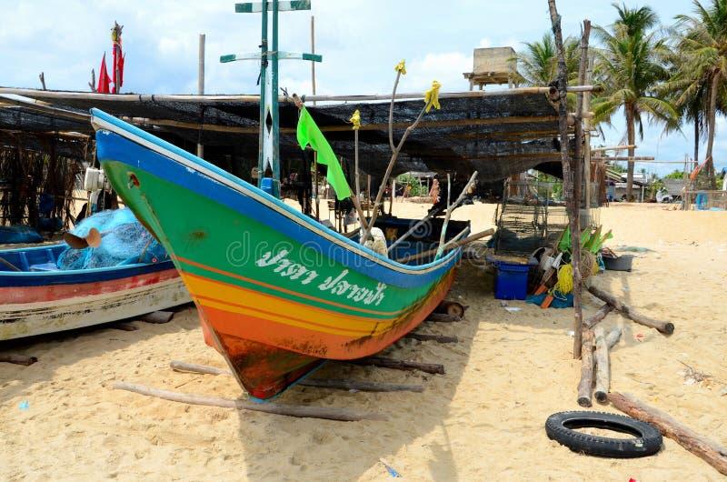 El arco tailandés del barco de pesca parqueado encendido abre una sesión la arena de la playa en el pueblo en Pattani Tailandia foto de archivo libre de regalías