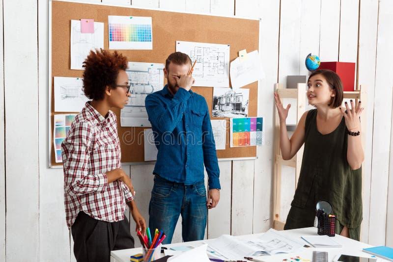 El argueing de los colegas, discutiendo dibujos, nuevas ideas en fondo de la oficina fotografía de archivo