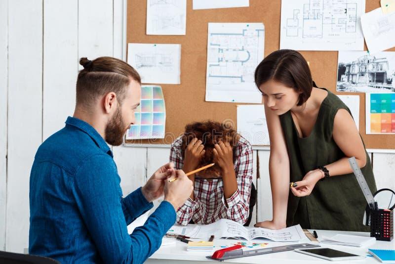 El argueing de los colegas, discutiendo dibujos, nuevas ideas en fondo de la oficina imagen de archivo