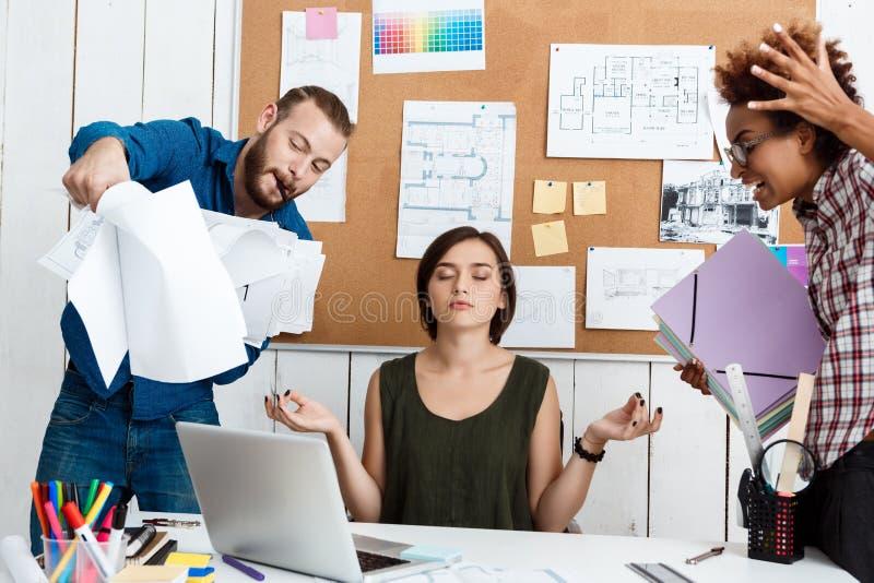 El argueing de los colegas, discutiendo dibujos, nuevas ideas mientras que el meditar de la muchacha Fondo de la oficina imagenes de archivo