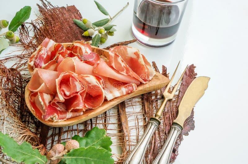 El aroma del jamón y de especias, cortado fino en una tabla blanca con los cubiertos y el vino tinto antiguos del pan imagenes de archivo
