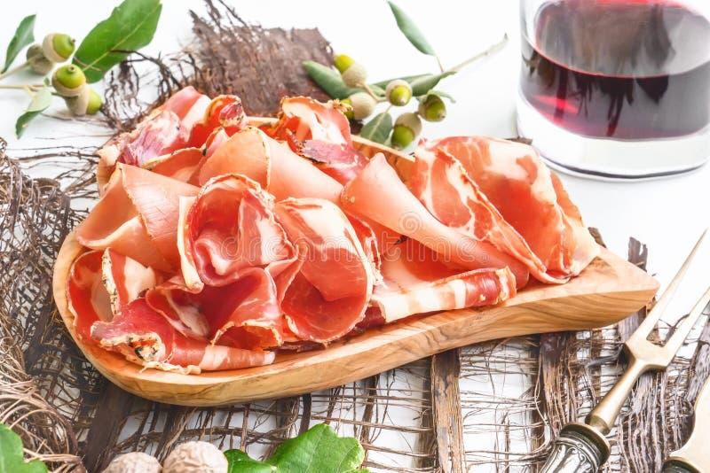 El aroma del jamón y de especias, cortado fino en una tabla blanca con pan y los cubiertos de la antigüedad imagen de archivo
