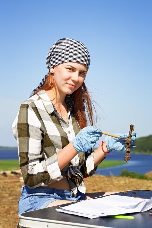 El arqueólogo hermoso de la muchacha despeja cuidadosamente el hallazgo con un cepillo imagenes de archivo