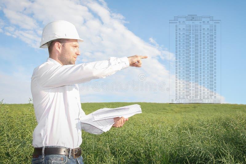 El arquitecto del ingeniero con los dibujos en el casco blanco muestra el emplazamiento de la obra del objeto futuro de las propi imágenes de archivo libres de regalías